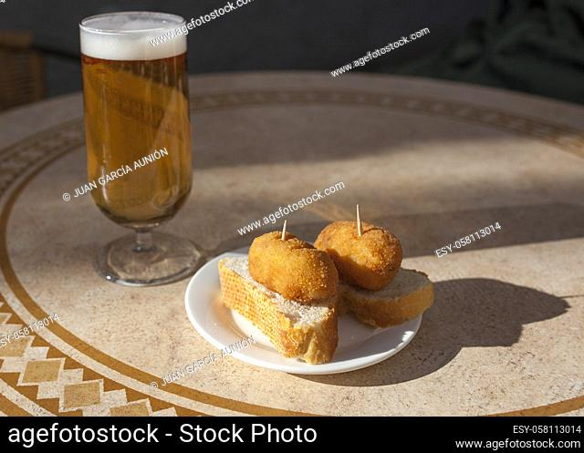 Spanish pinchos of croquettes close to glass of beer. Pincho served over sunny terrace table