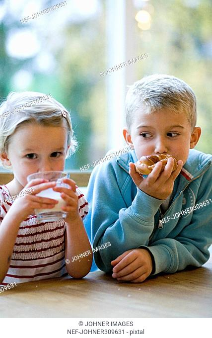 A boy and a girl drinking milk and eating rolls