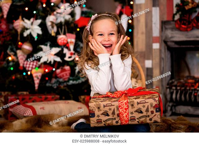 Happy pretty girl with gift box lies near Christmas tree in the room of the house. Merry Christmas and New Year