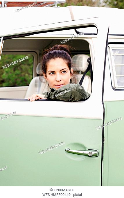 Young woman sitting in camperm looking out of window