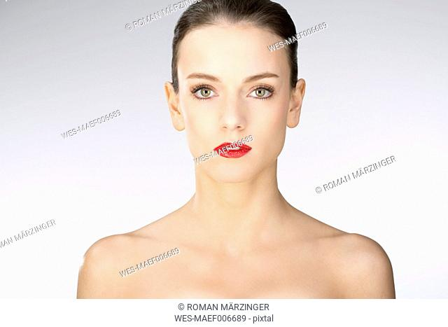 Portrait of young woman against white background, close up