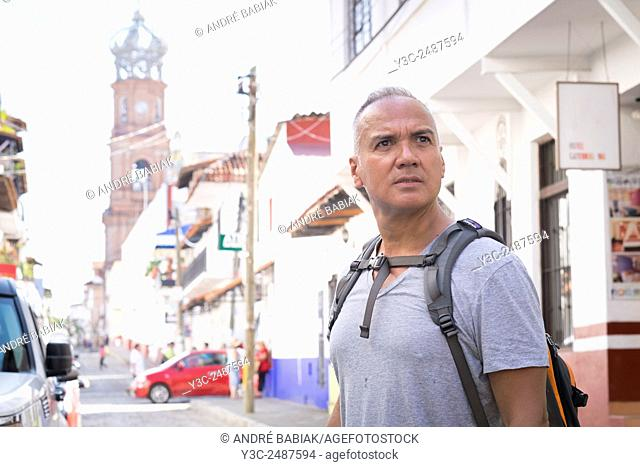Tourist in Puerto Vallarta, Mexico. Man with backpack, 55 years old, hispanic ethnicity