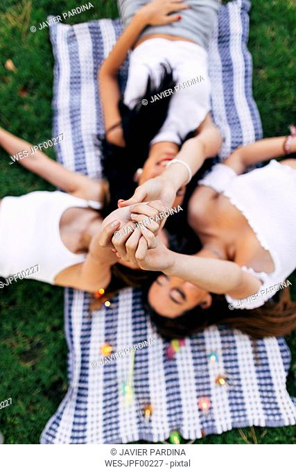 Friends in a park lying on blanket raising their arms