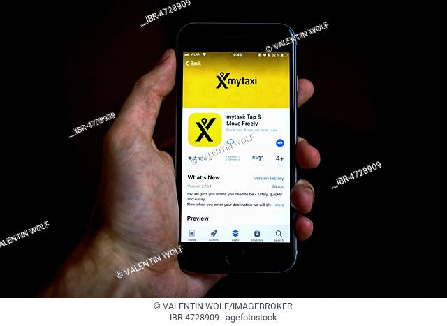 Hand holding an iPhone displaying the mytaxi app, taxi hauling app, in the Apple App Store, app icon, display, iPhone, iOS, smartphone, Germany