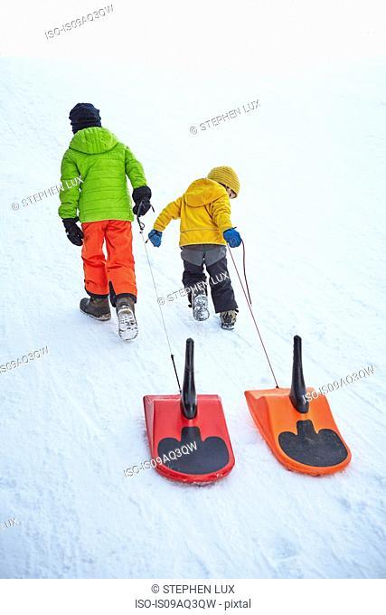 Boys pulling toboggan uphill