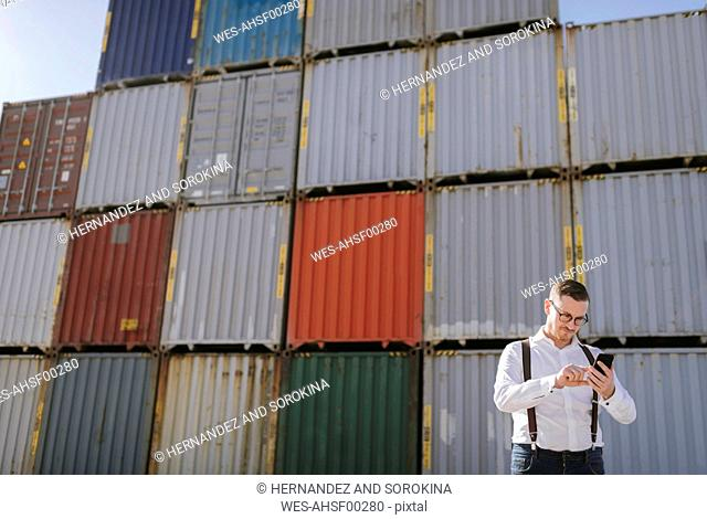 Manager in front of cargo containers on industrial site using cell phone