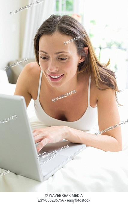 Smiling relaxed woman using laptop in bed