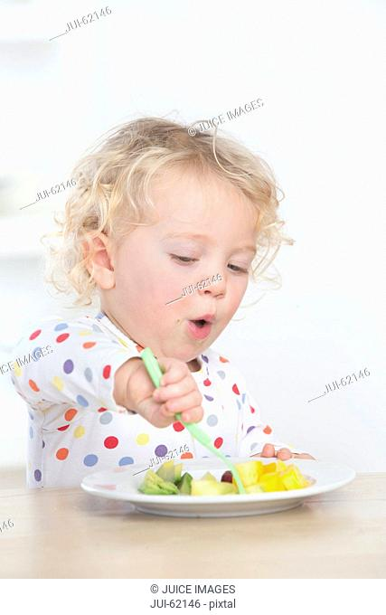 Determined baby eating fruit with fork