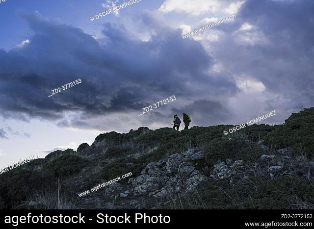Two mountaineers ascending the ridge between Les Agudes and Turó de l'Home. Montseny Natural Park. Catalonia. Spain