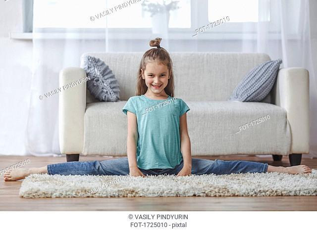 Full length portrait of smiling girl doing splits on rug in living room at home