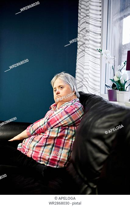 Thoughtful mentally challenged woman sitting on sofa
