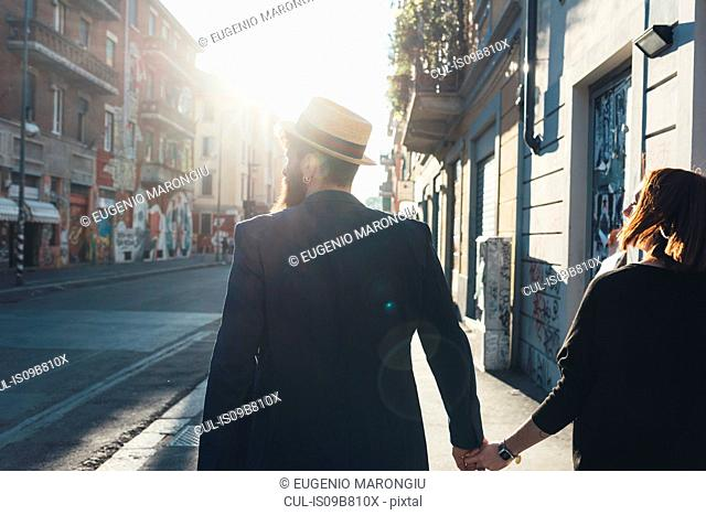 Rear view of cool couple strolling on sunlit street