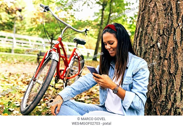 Smiling young woman looking on cell phone in a park in autumn
