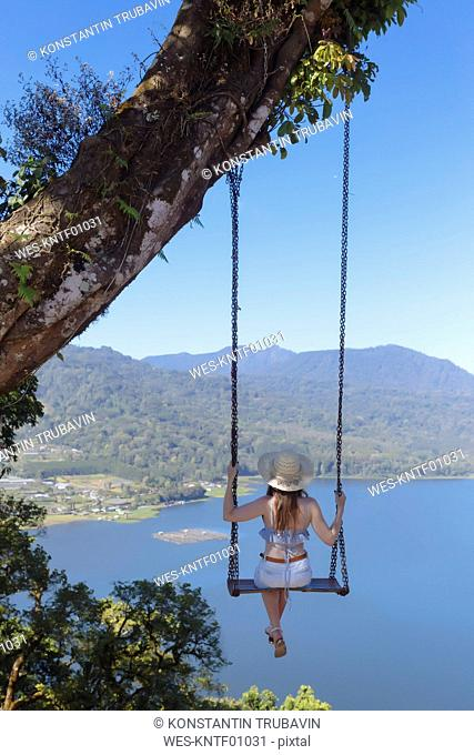 Indonesia, Bali, young woman sitting on a swing under tree overlooking coastal landsacpe