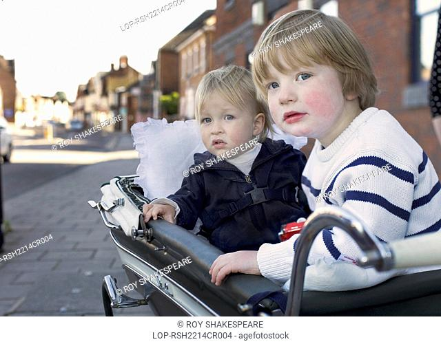 England, Hertfordshire, Hitchin. A 3 year old boy and an 18 month old boy in their perambulator