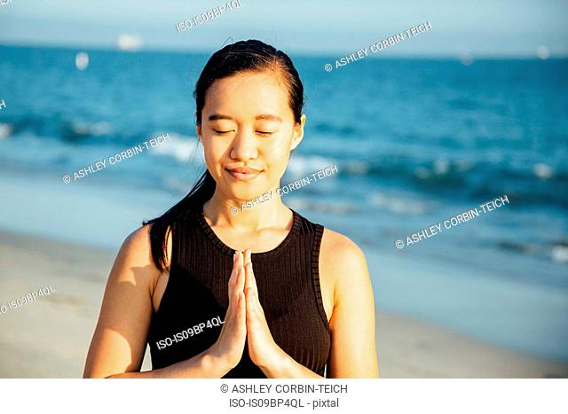 Woman with palms pressed together on beach