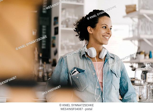 Young woman with headphones, working in coworking space