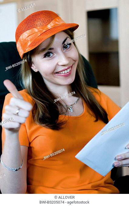 attractive young woman in an orange t-shirt and cap, holding a letter in her hand, signalizing ok
