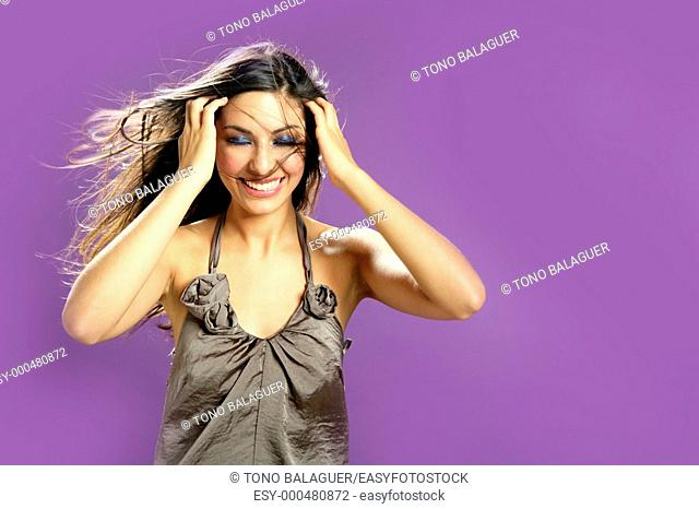 Brunette indian beautiful woman dancing at studio on purple background