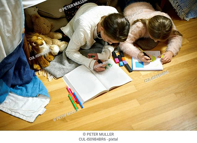 Two sisters lying on bedroom floor drawing in sketchbooks
