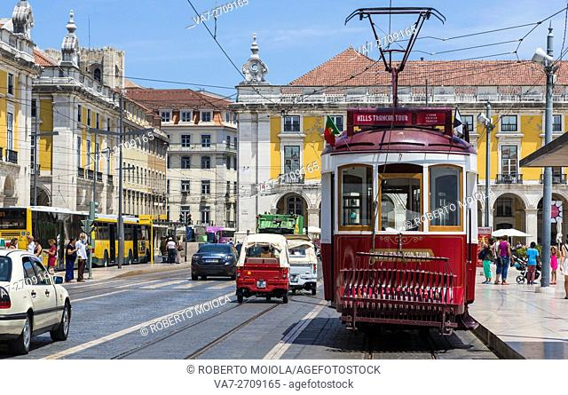 A typical red tram stops at the historical Praca Do Comercio square near the Tagus river Lisbon Estremadura Portugal Europe