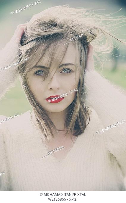 Beautiful young woman hands touching hair on a windy day