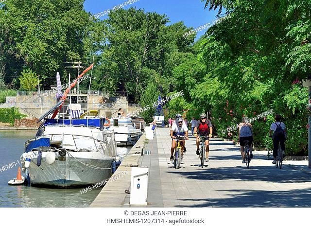 France, Herault, Beziers, Canal du Midi listed as World Heritage by UNESCO, New port, cyclists following pleasure boats alongside the quay downstream to the...