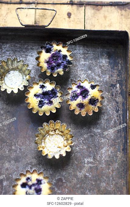 Blueberry friands in baking tins on a rustic tray