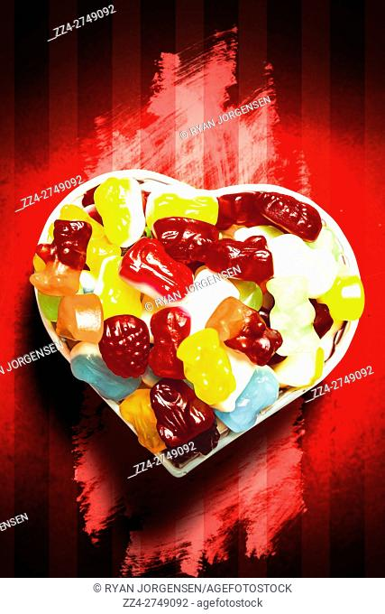 Top view of heart bowl full of colorful vivid jelly sweets on red paint splatter background. Love in sweet forms