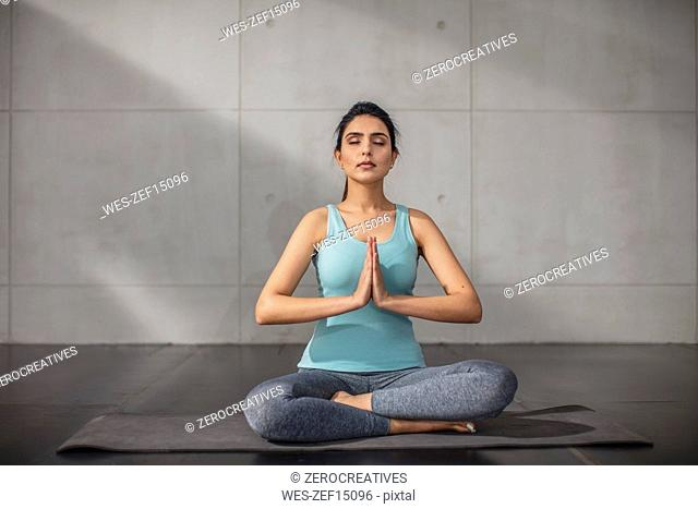 Young woman doing yoga exercise in studio