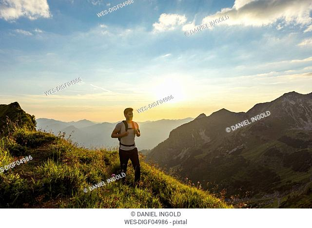 Germany, Bavaria, Oberstdorf, man on a hike in the mountains at sunset
