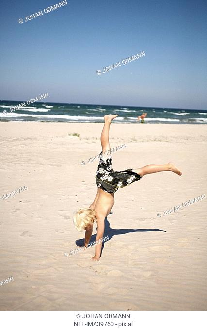 A boy standing on his hands on a beach