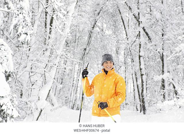 Young woman in snow, holding ski pole, smiling