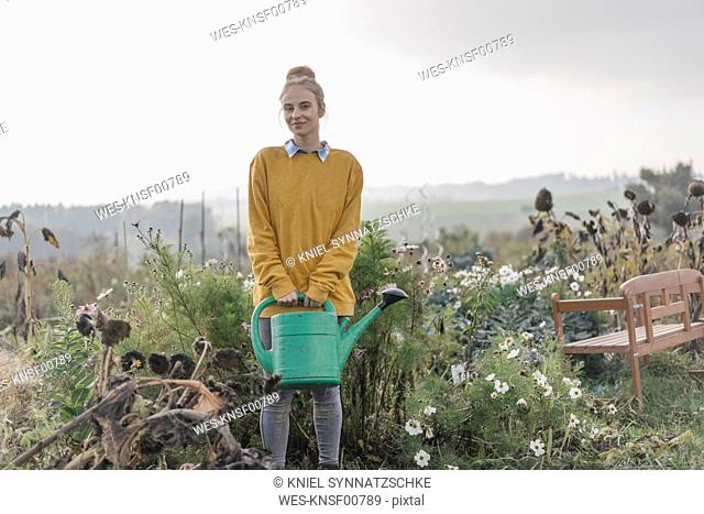 Smiling young woman holding watering can in cottage garden