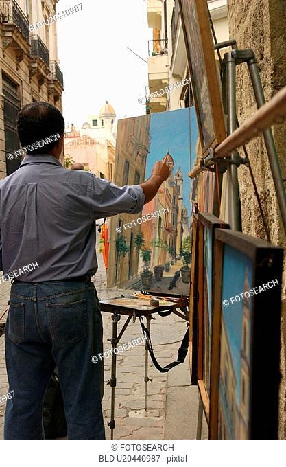 Rear view of a man painting outdoors, Havana, Cuba