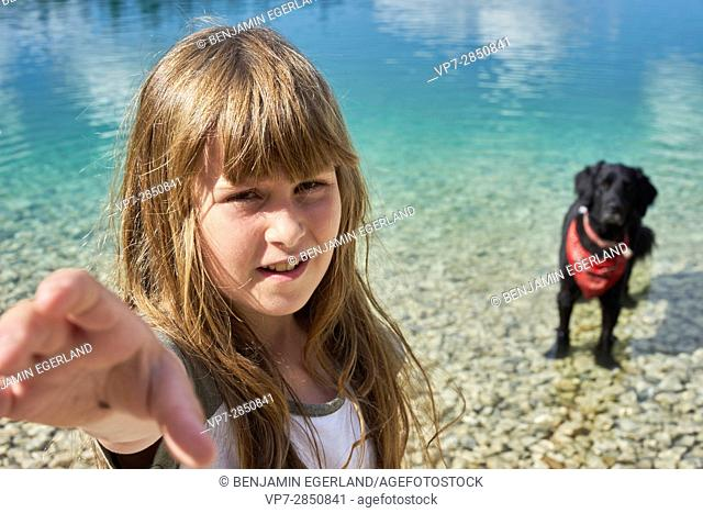 Young girl with her dog at lake