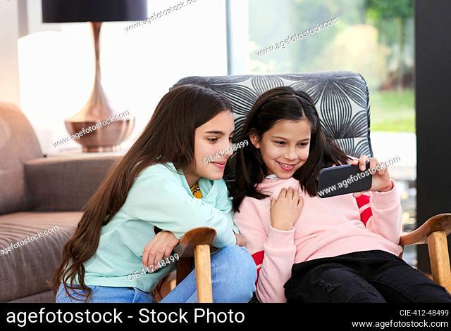 Sisters using smart phone in living room