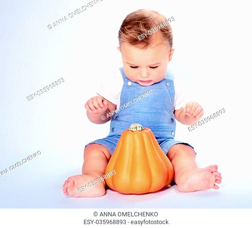 Cute little baby boy sitting in the studio over clean background and with wonder looking on the orange pumpkin, happy Thanksgiving day