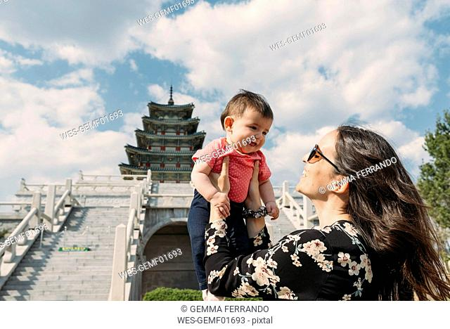 South Korea, Seoul, happy woman holding a baby girl in front of the National Folk Museum of Korea, inside Gyeongbokgung Palace