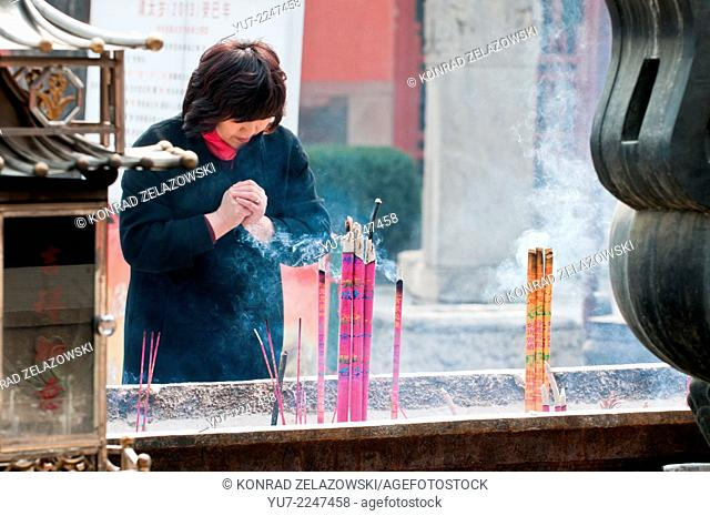 Woman praying in front of incense burner in taoist Dongyue Temple in Chaoyang District, Beijing, China