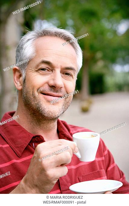 Portrait of smiling man with cup of coffee