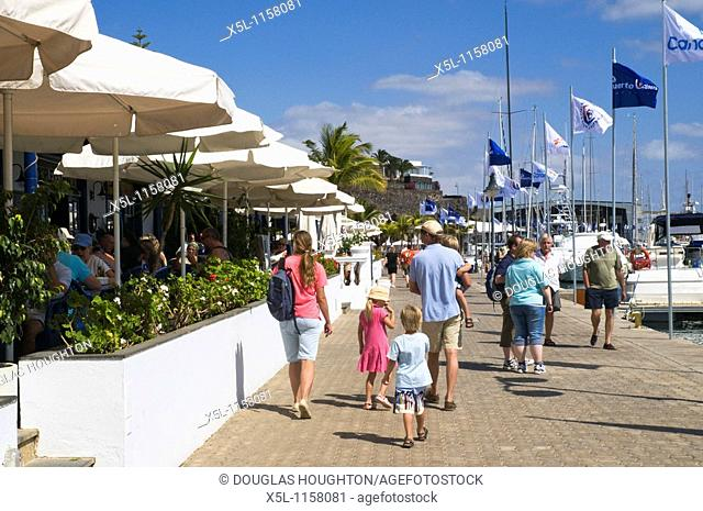 PUERTO CALERO LANZAROTE Tourist Holidaymaker family on marina prom walk past cafes