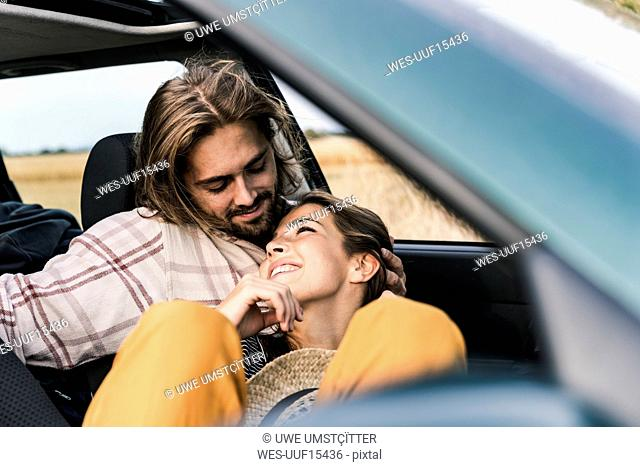Happy affectionate young couple in a car