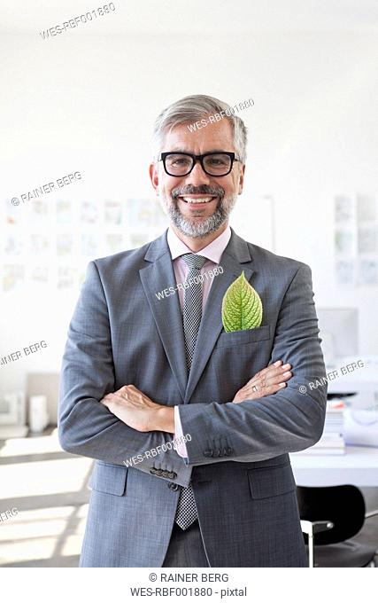 Portrait of smiling businessman with green leaf in his jacket pocket