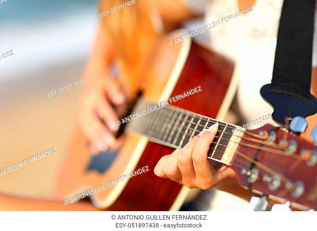 Closeup of a girl hands on the beach playing classic guitar
