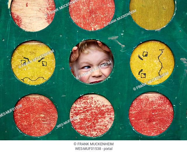 Portrait of little boy hiding on playground