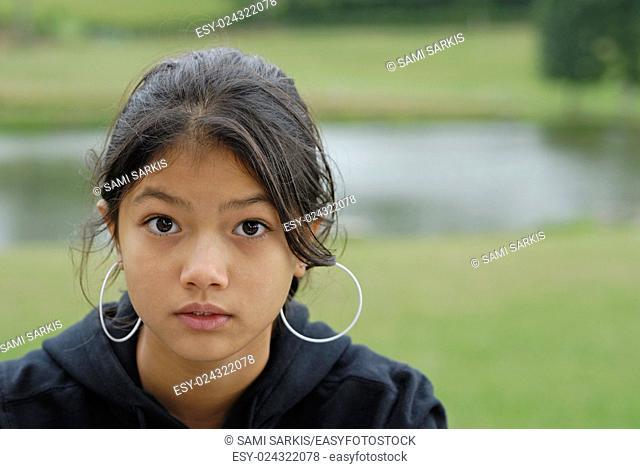 Eurasian girl (13) portrait, looking surprised at camera, France