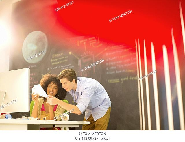 Business people examining model in office