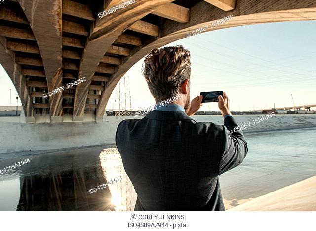 Businessman taking photograph using smartphone, Los Angeles river, California, USA