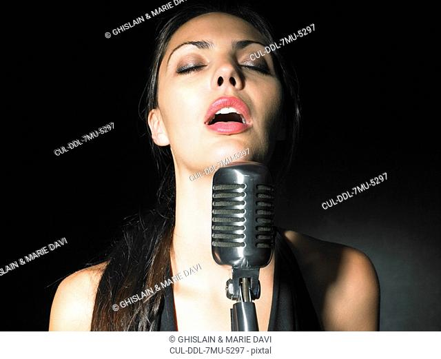 Female singer with microphone elegant black dress portrait